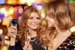 Szcz??liwe kobiety pij? w szk?ach przy noc klubem zdjęcie royalty free