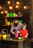 szcz??liwe ogrodniczki z wiosna kwiatami Rodzinny dzie? charcica Kwiat opieki podlewanie Glebowi u?y?niacze Ojciec i syn obrazy stock