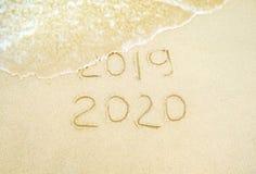 szcz??liwego nowego roku, 2020 i 2019 pisa? na piasku dok?d 2019 dostaje myj?cym daleko od fal? obraz royalty free