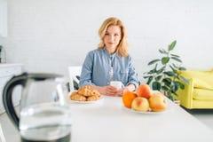 Szcz??liwej kobiety kulinarny ?niadanie na kuchni obraz royalty free
