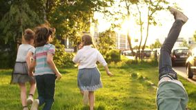 Szcz??liwi dzieci Cztery kolegi z klasy ściskali each inny i biegali w odległość przeciw tłu zieleni drzewa i zbiory wideo
