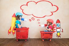 Szcz??liwi dzieci jedzie zabawkarskiego samoch?d w domu obraz stock