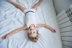 Szcz??liwi dzieciaki bawi? si? w bia?ej sypialni Ch?opiec, dziewczyna, brat i siostra jest ubranym pi?amy, bawi? si? na ? obraz royalty free