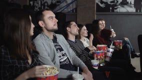 Szcz??liwi przyjaciele ogl?da film w teatrze Dobiera się i inny ludzie je popkorn i pije sodę podczas gdy oglądający film zbiory wideo