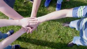 Szcz??liwi przyjaciele stawia ich r?ki na g?rze each inny na trawie na tle symbolizuje jedno?? i prac? zespo?ow? zbiory