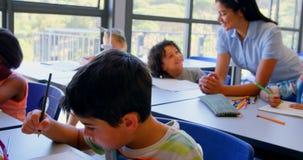 Szcz??liwi schoolkids oddzia?a wzajemnie z nauczycielem przy biurkiem w sali lekcyjnej 4k zbiory