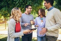 Szcz??liwi u?miechni?ci m?odzi przyjaciele chodzi outdoors w parkowego mienia cyfrowej pastylce zdjęcie stock