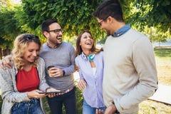Szcz??liwi u?miechni?ci m?odzi przyjaciele chodzi outdoors w parkowego mienia cyfrowej pastylce fotografia royalty free