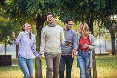 Szcz??liwi u?miechni?ci m?odzi przyjaciele chodzi outdoors w parkowego mienia cyfrowej pastylce zdjęcia stock