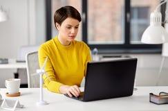 Szcz??liwy bizneswoman z laptopem pracuje przy biurem zdjęcia stock