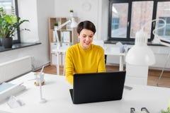 Szcz??liwy bizneswoman z laptopem pracuje przy biurem zdjęcia royalty free