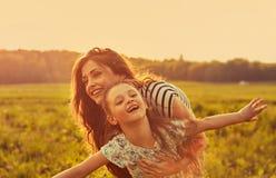 Szcz??liwy cieszy si? macierzysty przytulenie jej figlarnie roze?miana dzieciak dziewczyna na zmierzchu lata jaskrawym tle zbli?e fotografia stock