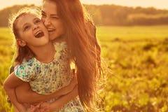 Szcz??liwy cieszy si? macierzysty przytulenie jej figlarnie roze?miana dzieciak dziewczyna na zmierzchu lata jaskrawym tle zbli?e obraz stock