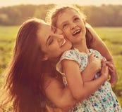 Szcz??liwy cieszy si? macierzysty przytulenie jej relaksuj?ca joying dzieciak dziewczyna na zmierzchu lata jaskrawym tle zbli?eni obraz stock