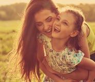 Szcz??liwy cieszy si? macierzysty przytulenie jej relaksuj?ca joying dzieciak dziewczyna na zmierzchu lata jaskrawym tle zbli?eni obrazy royalty free