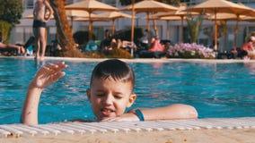 Szcz??liwy dziecko P?ywa w basenie z b??kitne wody przy hotelem swobodny ruch zdjęcie wideo