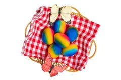Szcz??liwy Easter dekoracji t?o Odgórny widok kolorowi Easter jajka w koszu na czerwonej w kratkę pielusze i dwa motylach zdjęcia royalty free