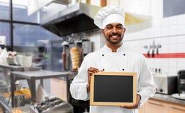 Szcz??liwy indyjski szef kuchni z chalkboard przy kebabu sklepem zdjęcia royalty free