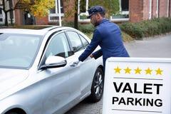 Szcz??liwy M?ski lokaj Otwiera Samochodowego drzwi obraz royalty free