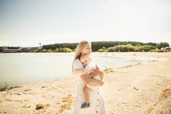Szcz??liwy macierzysty huges dziecko Matka trzyma dziecka w jej r?kach, dziecka przytulenia mama, w g?r? fotografia stock