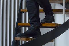 Szczegół jest ubranym czarnych cajgi i czarnych zamszowy buty chodzi w dół wewnętrznego schody mężczyzna ceglanego pojęcia przest obraz royalty free
