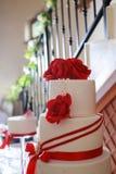 Szczegół biały ślubny tort z czerwonymi jadalnymi kwiatami Fotografia Stock