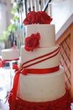 Szczegół biały płatowaty ślubny tort z czerwonymi jadalnymi kwiatami Obrazy Royalty Free