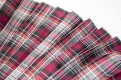 Szczegół nowa szkocka krata plisująca mody spódnica: czerwień, ono wałkoni się, szara tartanu mundurka szkolnego tkaniny bawełna, obrazy stock