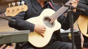 Szczegół ręka artysta ubierał w czerni bawić się sznurki gitara akustyczna Zdjęcia Stock