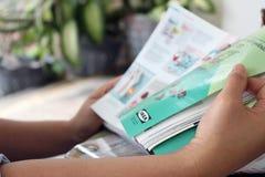 Szczegół ręki kobieta czyta IKEA katalog outdoors Zdjęcia Stock