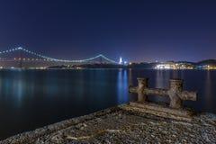 Szczegół stary molo w bankach Tagus Rzeczny Rio Tejo z 25 Kwietnia most na tle przy nocą Zdjęcie Stock