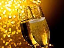 Szczegół szampańscy flety z złotymi bąblami na ciemnym złotym lekkim bokeh tle fotografia stock