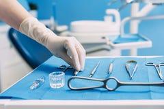 Szczegół trzyma stomatologicznych narzędzia w stomatologicznej klinice ręka Obraz Royalty Free