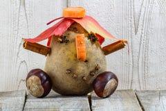 Szczegół zabawa kartoflany charakter z cisawymi jesień liśćmi na wh obraz stock