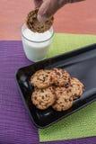Szczegół zamacza czekoladowego układu scalonego ciastko w dojnym szkle ręka zdjęcia royalty free