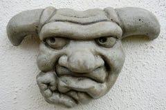 Szczegółowy wizerunek kamieniarka garguleca grimacing twarz, widzieć obwieszenie na outside ścianie obraz stock