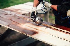 szczegóły odnawi ogrodzenie kiść pistolet i męskie ręki Woodwork szczegóły z malarzem Fotografia Royalty Free