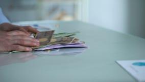 Szczerego mężczyzna kładzenia pieniądze stół, oddawanie plecy, płaci kredyt, obca waluta zbiory wideo