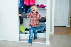 Szczery naturalny portret śmieszny śliczny biały Kaukaski chłopiec berbeć w garderobie robi śmiesznej twarzy pokazuje jęzor w dom Obrazy Stock