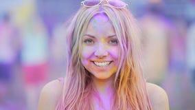 Szczery uśmiech rozochocona młoda kobieta ma zabawę przy podniecającym koloru festiwalem zbiory