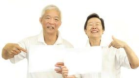 Szczęśliwa Azjatycka starsza para trzyma białego puste miejsce znaka przygotowywający dla pro Zdjęcie Stock