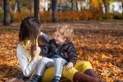 Szczęśliwa chłopiec i jego matka cieszy się w parku Zdjęcia Stock