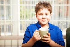 Szczęśliwa chłopiec pije kawę Zdjęcia Royalty Free