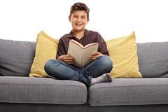 Szczęśliwa chłopiec trzyma książkę i patrzeje kamerę sadzał na kanapie Zdjęcia Royalty Free