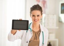Szczęśliwa doktorska kobieta pokazuje pastylka komputerowi osobistemu pustego ekran Fotografia Royalty Free
