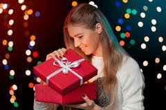 Szczęśliwa dziewczyna otwiera Bożenarodzeniowego pudełko który jest rozjarzonym inside Bożenarodzeniowy prezent Fotografia Stock