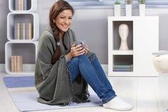 Szczęśliwa dziewczyna z koc i herbatą Zdjęcia Stock