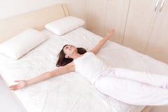 Szczęśliwa kobieta kłama puszek na jej łóżku Zdjęcia Royalty Free