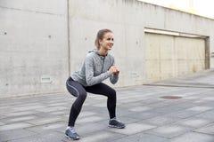 Szczęśliwa kobieta robi kucnięciom i ćwiczy outdoors Zdjęcia Royalty Free