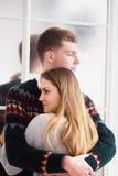 Szczęśliwa kobieta ubierał w pulowerze stawia jej głowę na ramieniu mężczyzna Obrazy Royalty Free